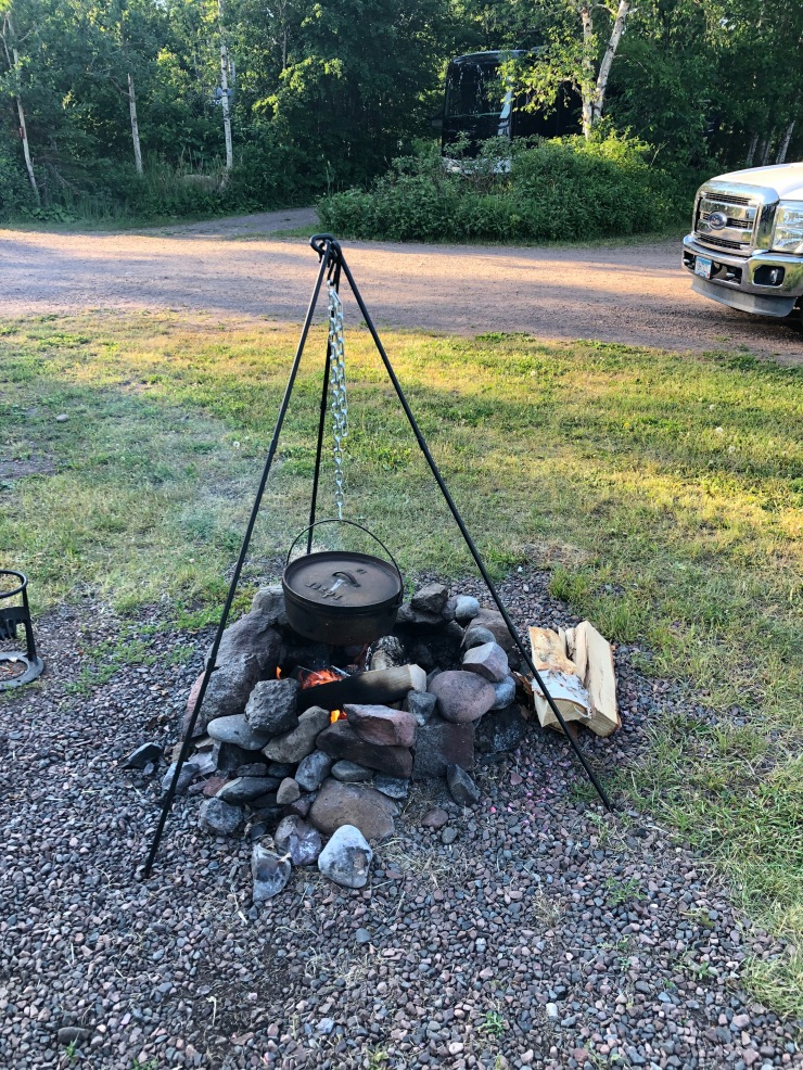 Using a tripod to hold a Dutch oven over a campfire to cook Jambalaya