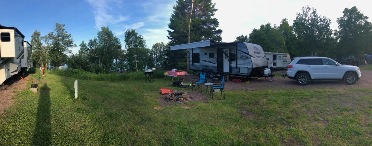 Panoramic photo of site 12B with trailer and Jeep